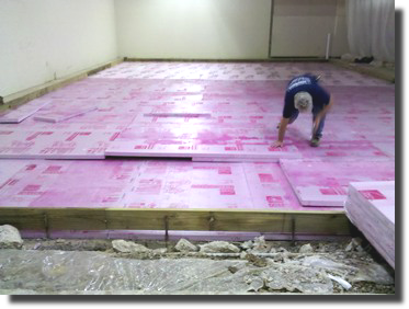 Applying insulation for a refrigerated room.
